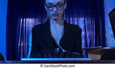 beautiful girl working with computer in leather gloves in...