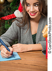 Beautiful girl writing New Year and Christmas congratulation