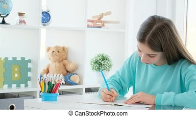 Beautiful girl writing with pencil in copybook at home