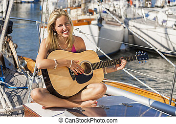 Beautiful Girl Young Woman Playing Guitar on a Boat