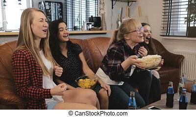 Beautiful girlriends watch soap opera on TV. Girls smile and...