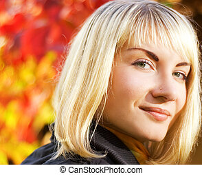 Beautiful girl's close-up portrait over abstract autumn background
