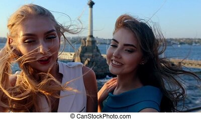 Beautiful girls doing selfie on the mobile phone on the background of the monument to the scuttled ships