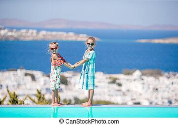 Beautiful girls enjoy greek vacation on Little Venice background.