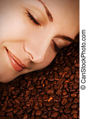 Beautiful girl's face over coffee beans