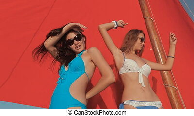 Beautiful girls in bikini having fun on a yacht with red sails