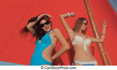 Beautiful girls in bikini having fun on a yacht with red sails
