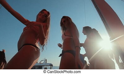 Beautiful girls in bikini relaxing on a yacht in the middle of the sea