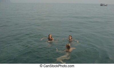 Beautiful girls in bikinis swimming and diving into the sea