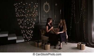 Beautiful girls in elegant dresses emotionally speak in a Christmas interior
