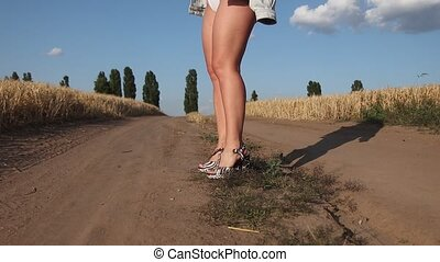 beautiful girls legs in heels on a country road, female beauty