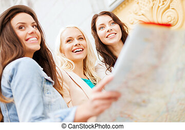 beautiful girls looking into tourist map in city - holidays ...