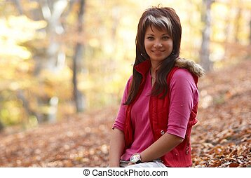 Beautiful girl\'s portrait with leaves in the autumn park