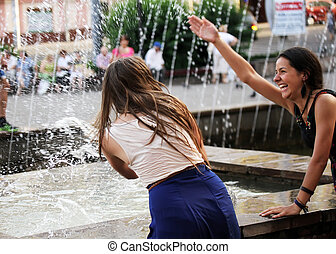 Beautiful girls relaxing with a fountain .
