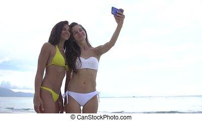 Beautiful girls taking selfie using phone on beach smiling and enjoying vacation