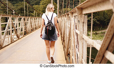 Beautiful girls traveling, walking on a bridge