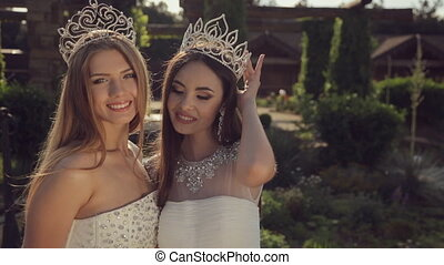 Beautiful girls wearing a crown and in white dresses cute smiling in the park