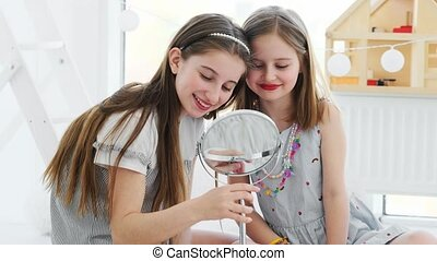 Beautiful girls kids with painted red lips smiling to mirror