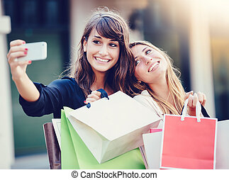 "Beautiful girls with shopping bags taking a ""selfie"" with..."