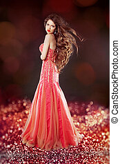 Beautiful glam with long hair posing in red dress over bokeh...
