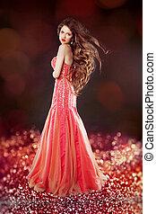 Beautiful glam with long hair posing in red dress over bokeh bri
