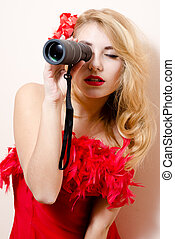 beautiful glamor young blond lady sexy attractive pin up girl having fun looking peering in spyglass telescope at copy space with red flower in her hair on white background closeup portrait image