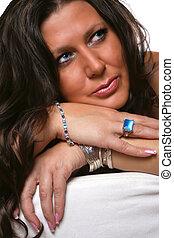 beautiful glamorous blue eyed brunette woman with blue stoned jewelry