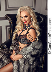 Beautiful glamour blond woman in sexy lingerie sitting in black armchair in luxury modern interior. Beauty glamour fashion style photo portrait.