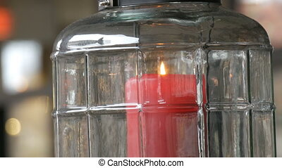 Beautiful glass candlestick with a big red burning wax candle of red color which is inside the candlestick and stands on the table of the street cafe