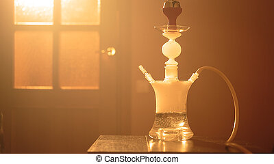 glass hookah on a table in the room