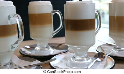 Beautiful glasses with coffee latte and big foam in the cafe...