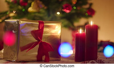 Beautiful gold gift box with red ribbon and burning candles on Christmas night