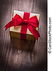 beautiful golden gift box with red ribbon on vintage brown woode