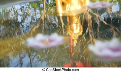 Beautiful golden reflection of the Buddha statue in a water,...