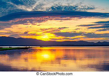Beautiful golden sky in the morning with sunrise over mountain range and lake or river. Landscape of reservoir and mountain. Peaceful, calm and tranquil background. Stunning and majestic view.