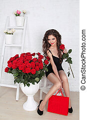 Beautiful gorgeous smiling woman with bouquet of red roses and gift box. Valentine's day love concept.