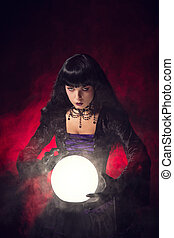 Beautiful gothic style fortune teller with a crystal ball, ...
