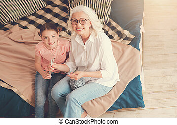 Beautiful granny and daughter smiling into camera while knitting