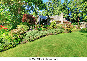 Beautiful green front garden with brown house.