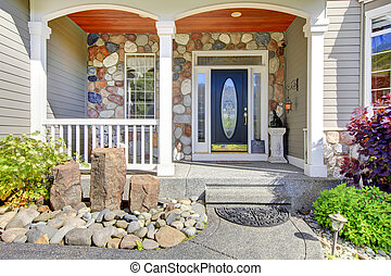 Beautiful grey new classic home entrance exterior with natural stone.