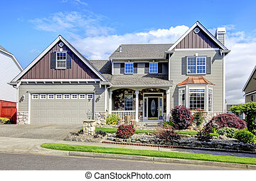 Beautiful grey new classic home exterior with natural stone.