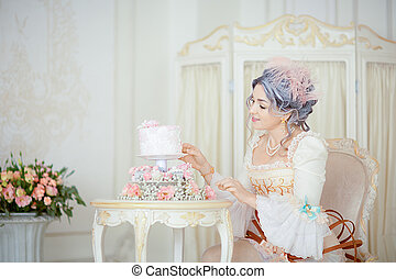 Beautiful greyhead woman in Rococo dress posing in front of historic background while decorating a cake