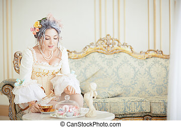 greyhead woman in Rococo dress posing in front of pink...