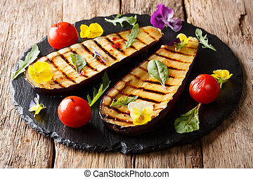 beautiful grilled eggplant served with tomato, herbs and edible flowers close-up. horizontal