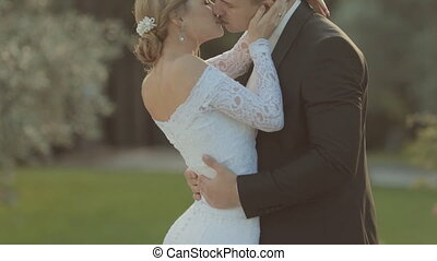 Beautiful groom gently hugs the waist of bride, kissing her and they laughing