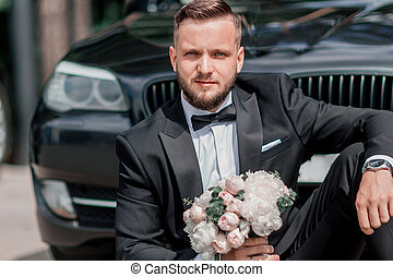 beautiful groom sitting near the wedding car.