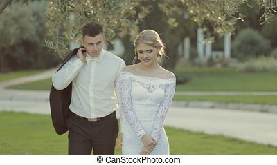 Beautiful groom with a jacket in his hands coming to the bride and kisses her
