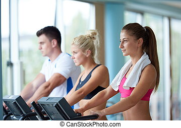 friends  exercising on a treadmill at the bright modern gym