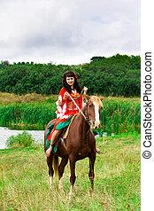 Beautiful gypsy girl riding a horse