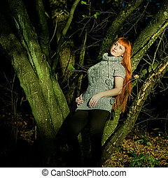 Beautiful-haired woman is leaning on a tree